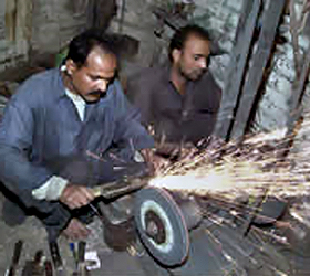 Knives being sharpened on eve of Eidul Azha