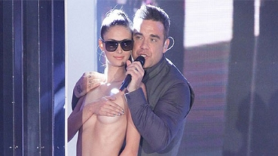 Robbie Williams Cavorts on Stage With Topless Dancer