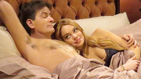 Lindsay Lohan shows off her cleavage in low cut lacy bra in bedroom scene with Charlie Sheen
