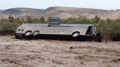 Tour bus flips over in wash amid Ariz. rain storm