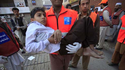 Rescue workers carry a boy, who was injured in a suicide bomb blast, to the Lady Reading Hospital for treatment in Peshawar