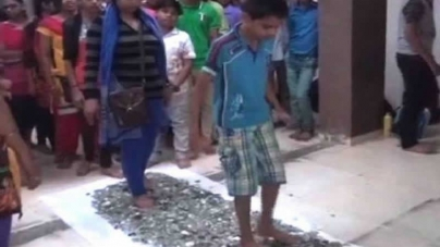Indian students walk barefoot on broken glass